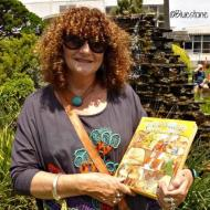 Claire Jennings still has the book she received as a child at one of the FJ Christmas Parties.  It inspired a life long interest in children's literature.  Claire is in the FJ gardens with her book at the 2015 community Christmas party in the gardens.  Photo:Bluestone Magazine